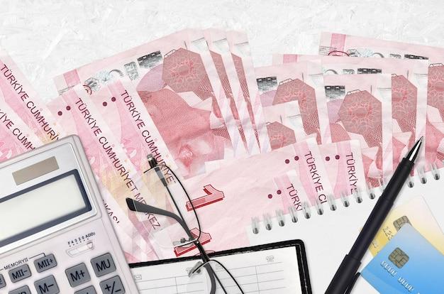10 turkse lira's rekeningen en rekenmachine met bril en pen. belastingbetalingsseizoenconcept of investeringsoplossingen.