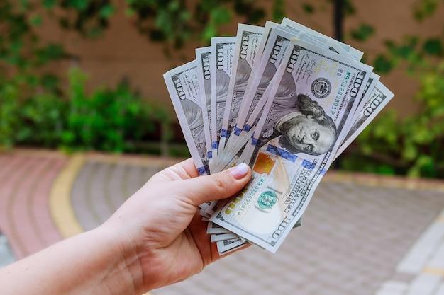 100 - dollarbiljetten in de handen van een vrouw.