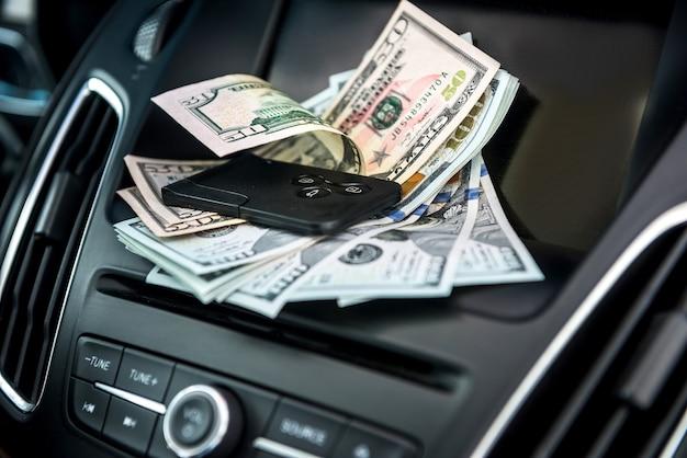 100 dollarbiljetten met autosleutel in auto. omkopen of koop huurconcept. contant geld in auto