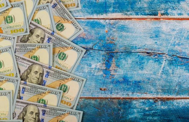 100 dollars bankbiljettenrekeningen op blauwe oude houten achtergrond