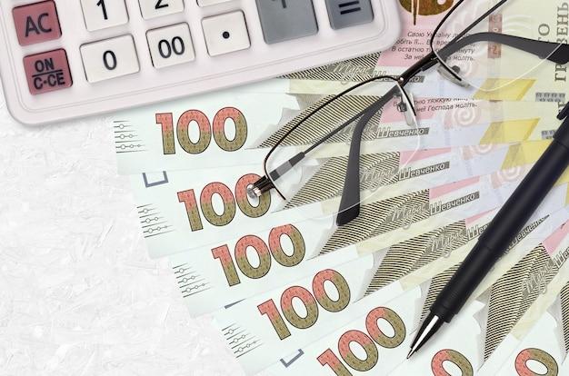 100 oekraïense hryvnia's rekeningenventilator en rekenmachine met bril en pen.