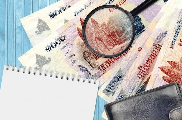 1000 cambodjaanse riels biljetten en vergrootglas met zwarte portemonnee en notitieboekje
