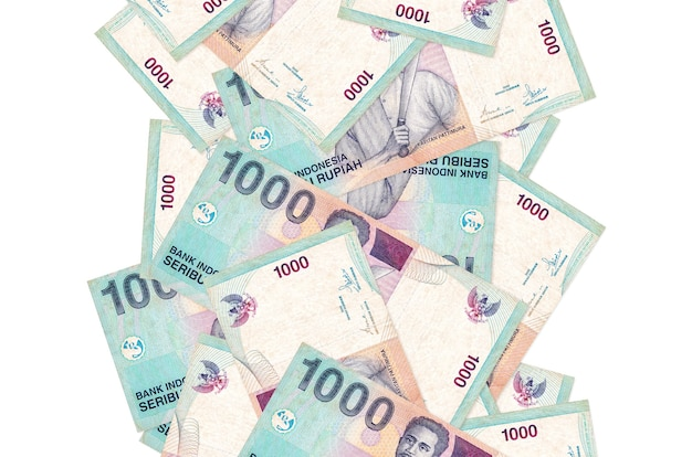 1000 indonesische roepia rekeningen vliegen naar beneden geïsoleerd op wit. veel bankbiljetten vallen met witte kopie ruimte aan de linker- en rechterkant