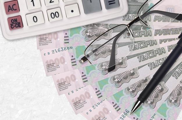 1000 russische roebels rekeningen ventilator en rekenmachine met bril en pen. zakelijke lening of belastingbetaling seizoen concept. financiële planning