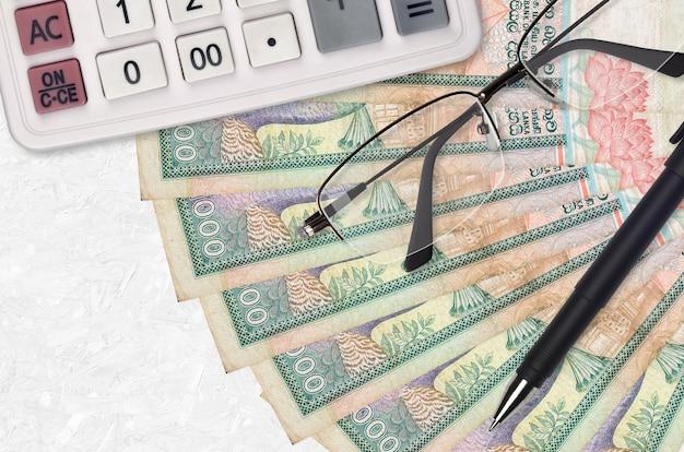 1000 sri lankaanse roepies rekeningen ventilator en rekenmachine met bril en pen. zakelijke lening of belastingbetaling seizoen concept. financiële planning