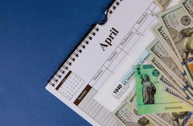 1040 belastingformulier met terugbetalingscontrole en close-up van de amerikaanse dollarbankbiljetten