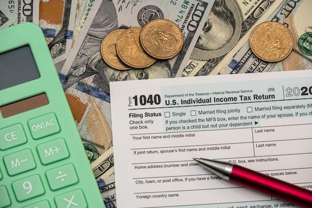 1040 individueel aangiftebiljet inkomstenbelasting met dollarbiljetten en rekenmachine. boekhoudkundig concept