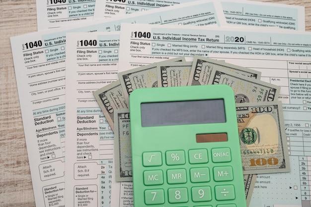 1040 individueel aangiftebiljet inkomstenbelasting met dollarbiljetten en rekenmachine.