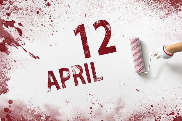 12 april. dag 12 van de maand, kalenderdatum. de hand houdt een roller met rode verf vast en schrijft een kalenderdatum op een witte achtergrond. lente maand, dag van het jaar concept.