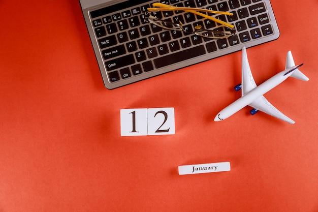 12 januari-kalender met accessoires op zakelijke werkruimte bureau op computertoetsenbord, vliegtuig, glazen rode achtergrond