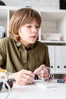 12-jarige jongen die een robotauto aan de tafel bouwt