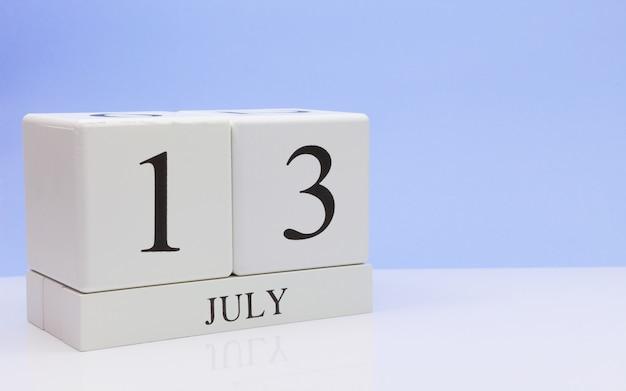 13 juli. dag 13 van de maand, dagelijkse kalender op witte tafel met reflectie, met lichtblauwe achtergrond.