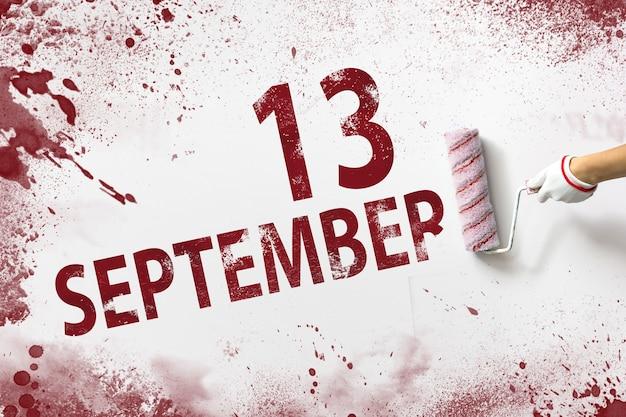 13 sept. dag 13 van de maand, kalenderdatum. de hand houdt een roller met rode verf vast en schrijft een kalenderdatum op een witte achtergrond. herfstmaand, dag van het jaarconcept.