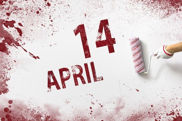 14 april. dag 14 van de maand, kalenderdatum. de hand houdt een roller met rode verf vast en schrijft een kalenderdatum op een witte achtergrond. lente maand, dag van het jaar concept.