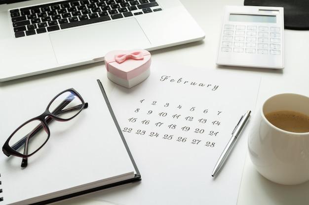 14 februari agenda op werkruimte met roze cadeau hart valentijnsdag kaart, kopje koffie.