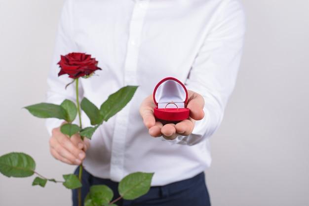 14 februari briljante diamanten steen vragen smoking concept. bijgesneden close-up foto portret van knappe gelukkige charmante kerel met kleine mooie doos in de hand geïsoleerd grijs oppervlak Premium Foto