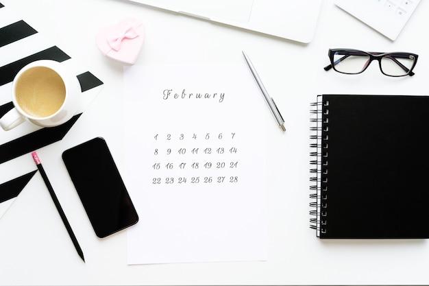 14 februari kalender op werkruimte met roze geschenk hart kopje koffie, flatlay