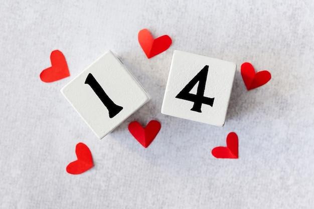 14 februari. witte houten kalender met rode harten bovenop valentijnsdag kaartmodel. plat leggen.