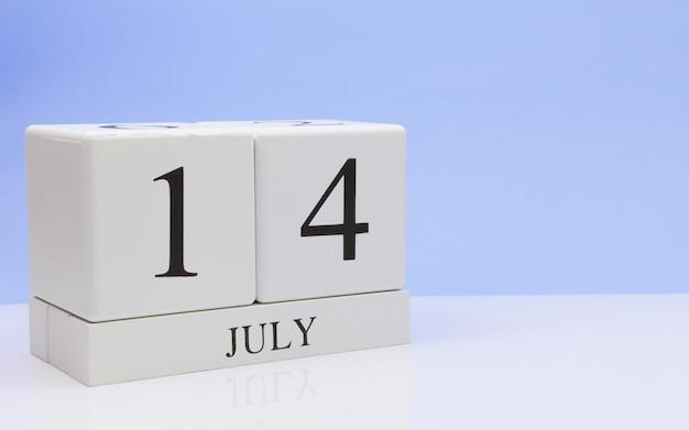 14 juli. dag 14 van de maand, dagelijkse kalender op witte tafel met reflectie, met lichtblauwe achtergrond.