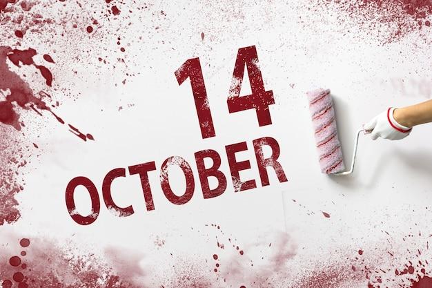 14 oktober. dag 14 van de maand, kalenderdatum. de hand houdt een roller met rode verf vast en schrijft een kalenderdatum op een witte achtergrond. herfstmaand, dag van het jaarconcept.