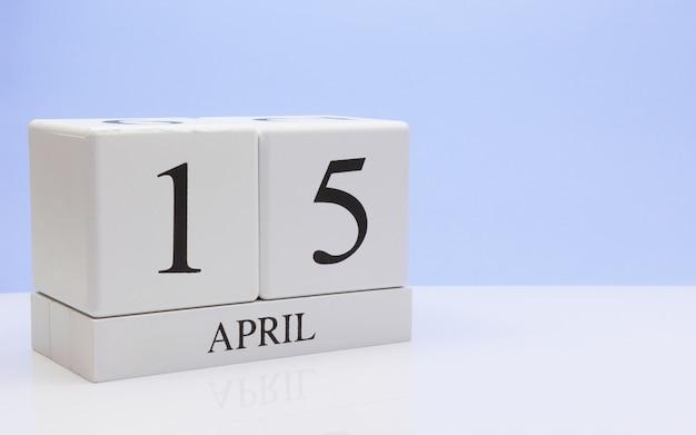 15 april. dag 15 van de maand, dagelijkse kalender op witte tafel met reflectie