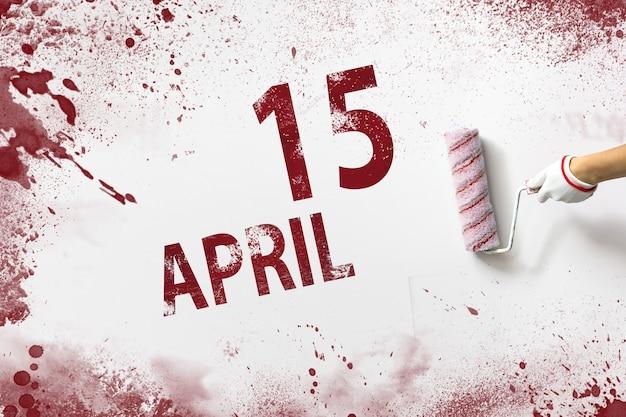 15 april. dag 15 van de maand, kalenderdatum. de hand houdt een roller met rode verf vast en schrijft een kalenderdatum op een witte achtergrond. lente maand, dag van het jaar concept.