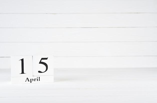 15 april, dag 15 van de maand, verjaardag, verjaardag, houten blokkalender op witte houten achtergrond met exemplaarruimte voor tekst.