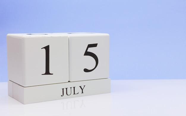 15 juli. dag 15 van de maand, dagelijkse kalender op witte tafel met reflectie, met lichtblauwe achtergrond.