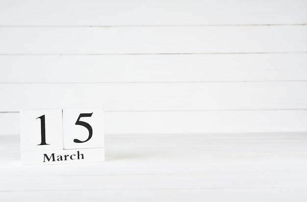 15 maart, dag 15 van de maand, verjaardag, verjaardag, houten blokkalender op witte houten achtergrond met exemplaarruimte voor tekst.