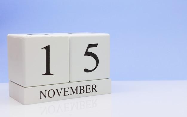 15 november. dag 15 van de maand, dagelijkse kalender op witte tafel met reflectie, met lichtblauwe achtergrond