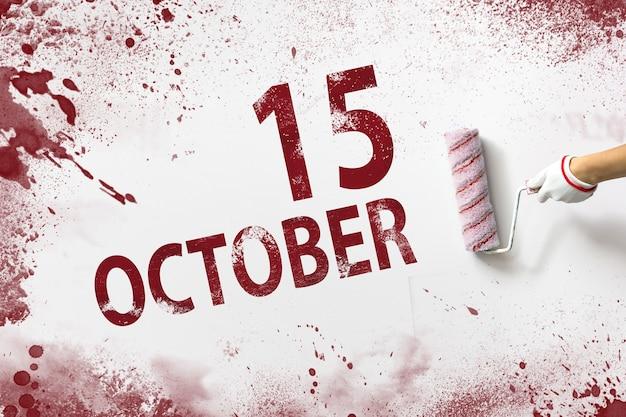 15 oktober. dag 15 van de maand, kalenderdatum. de hand houdt een roller met rode verf vast en schrijft een kalenderdatum op een witte achtergrond. herfstmaand, dag van het jaarconcept.