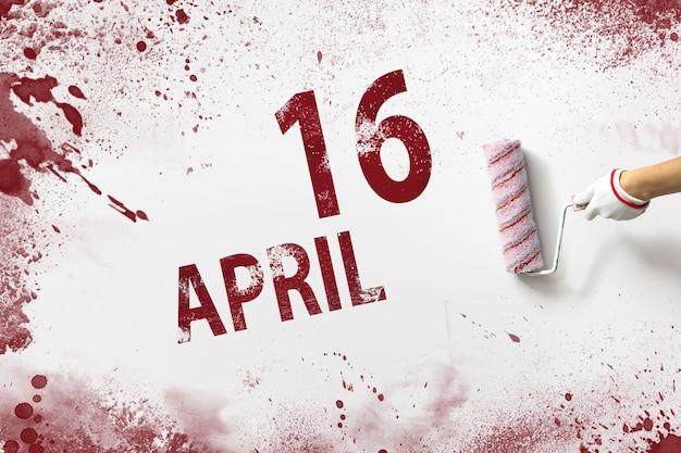 16 april. dag 16 van de maand, kalenderdatum. de hand houdt een roller met rode verf vast en schrijft een kalenderdatum op een witte achtergrond. lente maand, dag van het jaar concept.