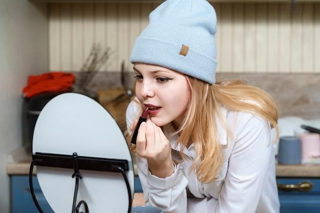 16-jarig meisje met een blauwe hoed schildert haar lippen voor de spiegel thuis in de keuken