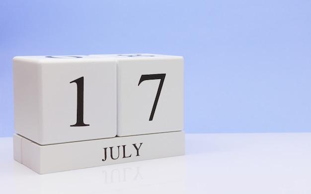 17 juli. dag 17 van de maand, dagelijkse kalender op witte tafel met reflectie, met lichtblauwe achtergrond.