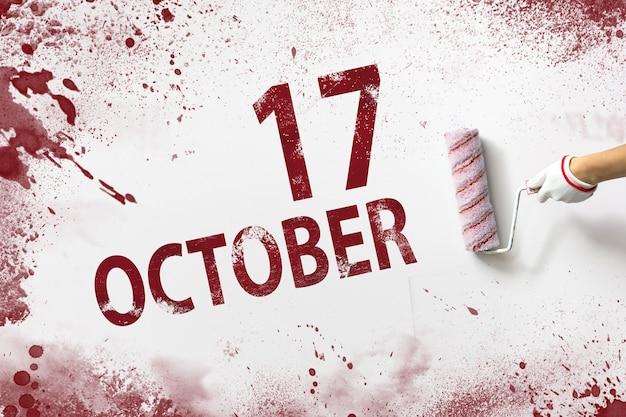 17 oktober. dag 17 van de maand, kalenderdatum. de hand houdt een roller met rode verf vast en schrijft een kalenderdatum op een witte achtergrond. herfstmaand, dag van het jaarconcept.