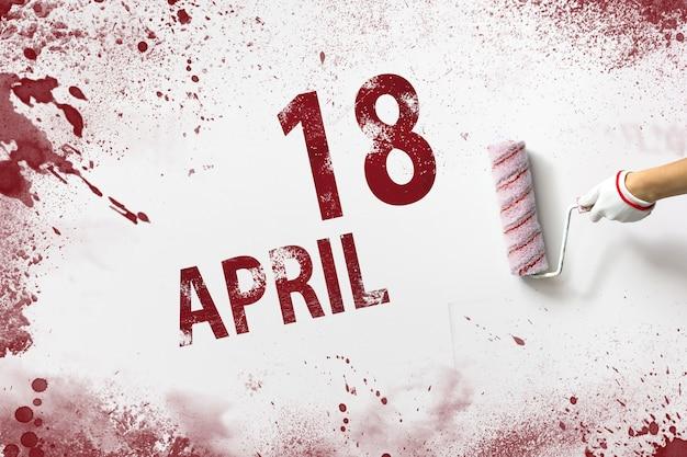 18 april. dag 18 van de maand, kalenderdatum. de hand houdt een roller met rode verf vast en schrijft een kalenderdatum op een witte achtergrond. lente maand, dag van het jaar concept.