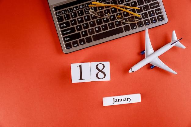 18 januari kalender met accessoires op zakelijke werkruimte bureau op computertoetsenbord, vliegtuig, glazen rode achtergrond