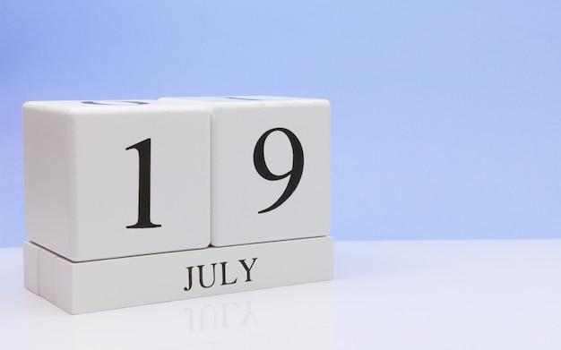 19 juli. dag 19 van de maand, dagelijkse kalender op witte tafel met reflectie, met lichtblauwe achtergrond.
