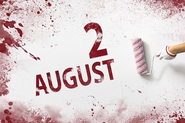 2 augustus. dag 2 van de maand, kalenderdatum. de hand houdt een roller met rode verf vast en schrijft een kalenderdatum op een witte achtergrond. zomermaand, dag van het jaarconcept.