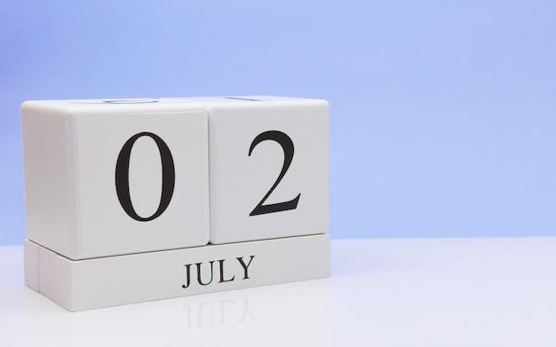 2 juli. dag 2 van de maand, dagelijkse kalender op witte tafel met reflectie, met lichtblauwe achtergrond.