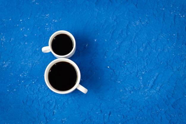 2 kopjes koffie op een blauwe achtergrond.