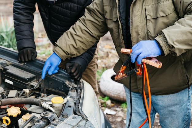 2 mechanische ingenieurs die de accu van de auto opladen met elektriciteit met behulp van startkabels buitenshuis. rode en zwarte jumper kabels in mannelijke handen van automonteur. mans in handschoenen werken in auto reparatie tankstation