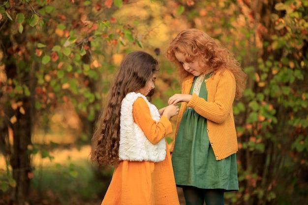 2 vrolijke brunette en roodharige meisjes voor een wandeling in het herfstpark.