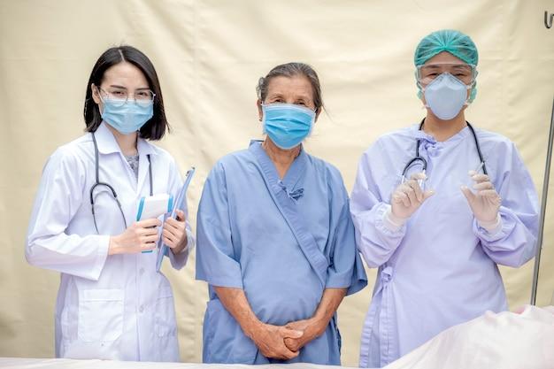 2 vrouwelijke artsen en senior patiënt stonden in het veldhospitaal en droegen maskers vanwege de covid 19-epidemie.