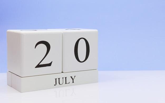 20 juli. dag 20 van de maand, dagelijkse kalender op witte tafel met reflectie, met lichtblauwe achtergrond.