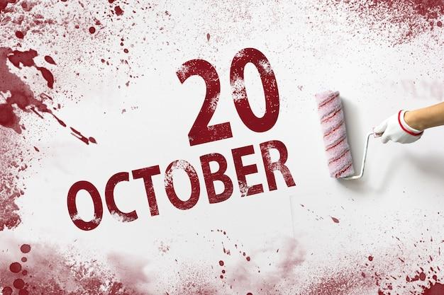 20 oktober. dag 20 van de maand, kalenderdatum. de hand houdt een roller met rode verf vast en schrijft een kalenderdatum op een witte achtergrond. herfstmaand, dag van het jaarconcept.