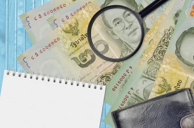 20 thaise baht-biljetten en vergrootglas met zwarte tas en notitieblok