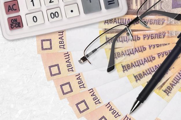 20 wit-russische roebels rekeningen ventilator en rekenmachine met bril en pen.