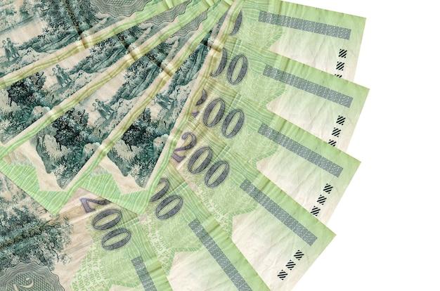 200 hongaarse forintbiljetten liggen geïsoleerd op een witte muur met kopie ruimte gestapeld in waaiervorm close-up. financiële transacties concept