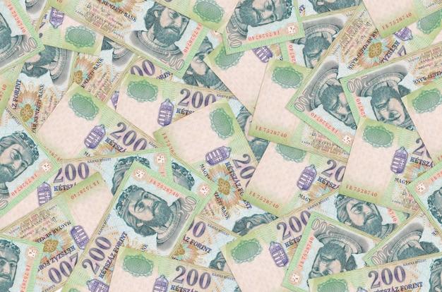 200 hongaarse forintbiljetten liggen op een grote stapel. rijke leven conceptuele muur. veel geld